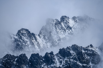 panoramic view of Tatra mountains in Slovakia covered with snow and hiding in mist