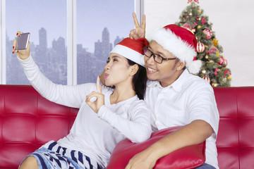 Asian couple taking a selfie near Christmas tree