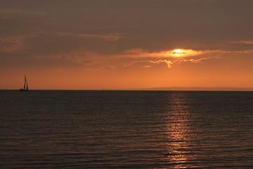 malerischer Sonnenuntergang mit Segelboot, dramatische Lichtstimmung am Meer