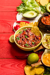 Vegetarian Mexican food concept: refried black and red beans. guacamole, salsa, chili, tortilla chips and fresh ingredients over vintage red rustic wooden background. Top view