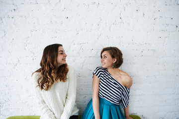 People, youth, happiness, joy and friendship. Two happy beautiful European young women friends or siblings wearing trendy clothes, posing at white brick wall, looking at each other and smiling Wall mural