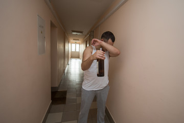 a drunk man stands and holds a bottle of alcohol in his hand and covers his face. Harmful habits, alcoholism