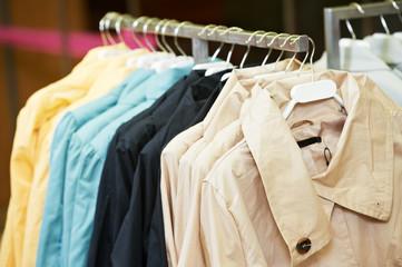 apparel shopping. rain coats hanging in clothing shop