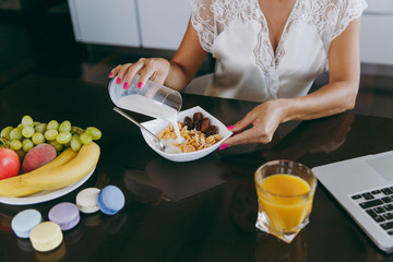 Young woman pouring milk into a bowl with cereal for breakfast with a laptop on the table. Eating at home close up