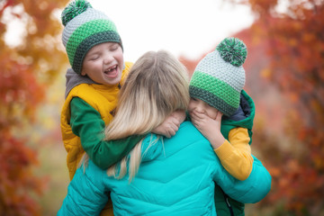 Two little boys gently hug his mother.A walk in the autumn woods.