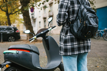 A tourist with a backpack is going to use an electric scooter through a mobile application in the phone and distally activate it. A popular vehicle in Berlin and Paris.
