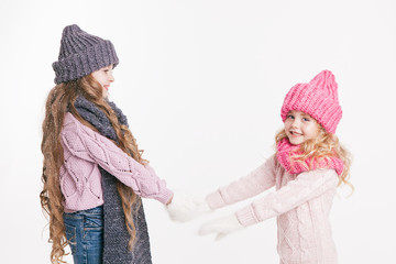 Two little sisters holding hands in winter clothes. Pink and grey. Family. Winter.