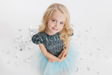 beautiful little girl with curly blonde hairstyle siting on the holiday party in dress with sequins. Silver foil on the floor. Concept Celebration. Isolated on white