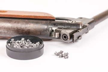 Box with metal air gun pellets and air gun with wooden kundak gunstock above white background