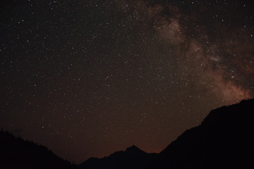 Milky Way on night sky with a lot of stars above mountains in Abkhazia