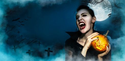Screaming vampire fangs female and hopding Halloween grinning face pumpkin mystery background, on Full moon midnight on smooky forest trees silhouette  cemetery and bats