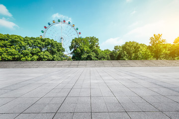Empty floor square and playground ferris wheel in the city park - fototapety na wymiar