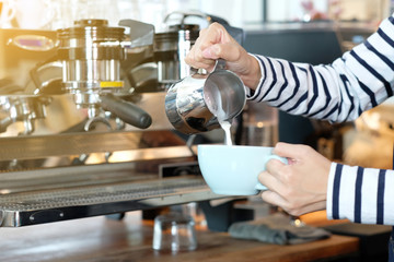 Women barista hand pouring milk into coffee cup at cafe counter, making coffee, latte art, food and drink concept