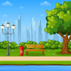 City park bench with green tree and streetlight near river bank