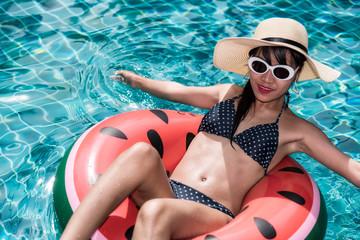 Beautiful girl Woman relaxing on watermelon lilo in pool