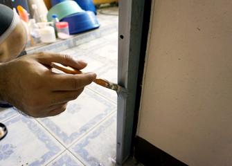 Worker hand with brush painting metal grey door
