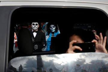 "A woman dressed up as ""Catrina"", a Mexican character also known as ""The Elegant Death"", takes part in a Catrinas parade while a woman takes a photograph from inside a vehicle in Mexico City, Mexico"