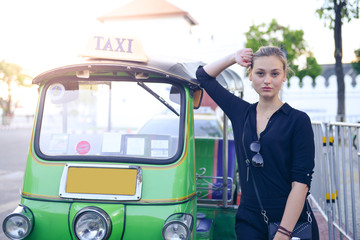 Beautiful woman tourist is traveling in Thailand and enjoy taking photo with Tuk Tuk.