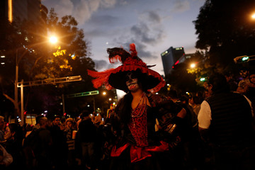 "A woman dressed up as ""Catrina"", a Mexican character also known as ""The Elegant Death"", takes part in a Catrinas parade in Mexico City, Mexico"