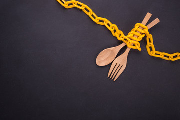 Yellow chain locked around the wooden spoon and fork on black stone board. Stop eating, eating control or diet concept