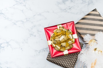 Top view of red glossy present box with golden bow and ribbon lay under white christmas tree on white marble floor,Holiday gift giving,leave space for adding text.