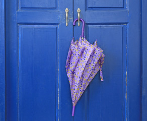 Close up Umbrella hanging on wood door. Ready to be picked up during rain.