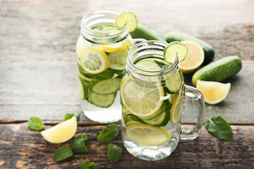Lemonade with cucumbers, lemons and mint leafs in glass jars on wooden table