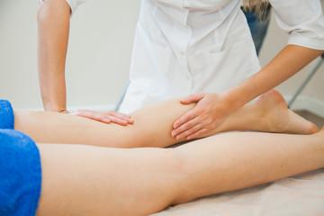 Young woman having massage at beauty spa salon. Beautician massaging female legs. Bodycare concept