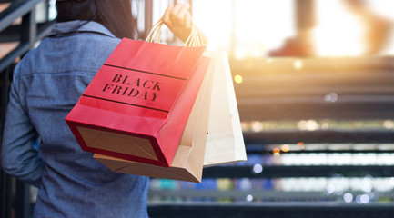 Rear view of woman holding Black Friday shopping bags while on up stairs outdoors mall background
