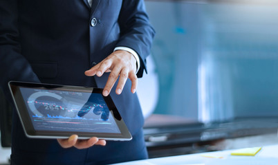 Analyzing data, Businessman working and checking market data in office, hand pointing on data presented in chart on tablet