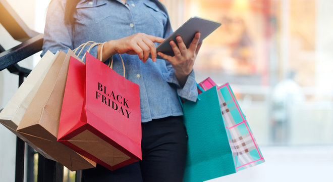Woman using tablet and holding Black Friday shopping bag while standing on stairs of mall background