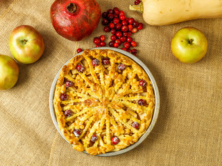 Fall traditional apple pie still life with pumpkin, cranberry and apples.