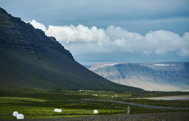 Travel to Iceland. Beautiful Icelandic landscape with green fields mountains, sky and clouds.