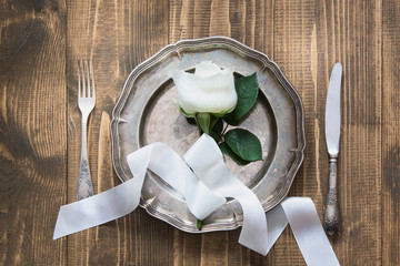 Romantic table setting with white rose as decor, vintage dishware, silverware and decorations on wooden board.