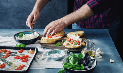 Man preparing Italian bruschetta with baked tomatoes, basil and cheese