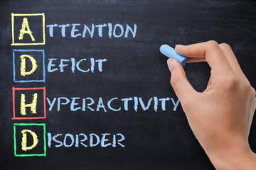 ADHD – attention deficit hyperactivity disorder handwritten by woman on blackboard