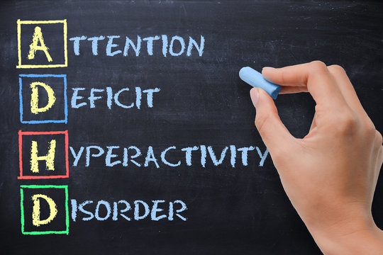 ADHD – attention deficit hyperactivity disorder handwritten by woman on blackboard