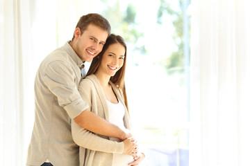 Pregnant woman and husband looking at camera