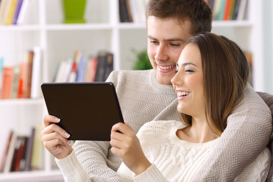 Couple watching streaming videos on a tablet at home