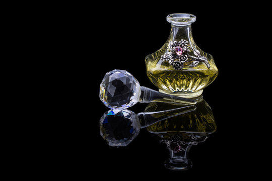 Close Up Shot Of Traditional Luxury Arabic Oud Oil Perfume In A Beautiful Handmade Clear Crystal Glass Jar Bottle and Glass Dropper Isolated On Black Background Antique Style, Text Space