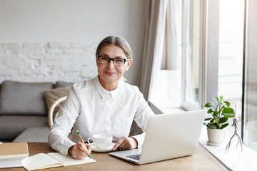 Attractive positive talented mature woman writer sitting in front of laptop and writing her new book about love, looking at camera with joyfull smile. Senior female teacher making notes in copybook