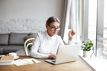 Beautiful concentrated middle aged businesswoman wearing rectangular glasses while keyboarding on generic laptop computer, sitting at her spacious office with notebook and cup of coffee on desk