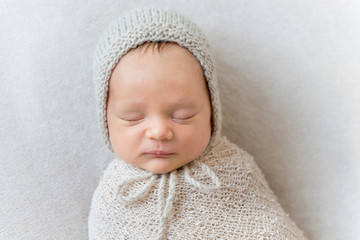 Lovely baby sleeping swaddled in a wrap, close-up