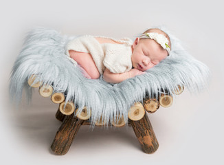 Newborn baby girl sleeps on small wooden crib.