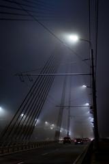 Bridge and traffic under lanterns in the mist during night.
