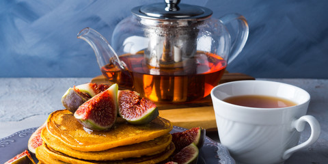 Stack of pumpkin pancakes with figs and honey and hot tea. Autumn food background on blue gray backdrop