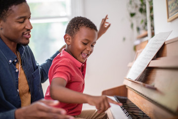 Father teaching Son to play the piano