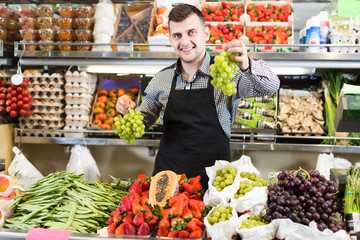 positive male seller showing assortment of grocery shop