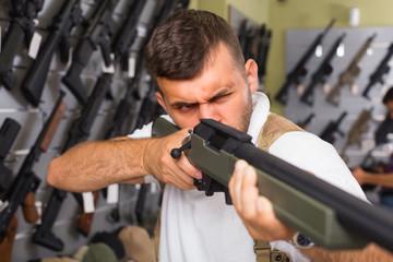 Portrait of man which is choosing air-powered gun
