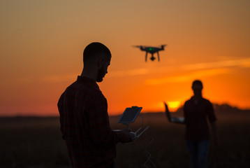 Man navigating drone above farmland